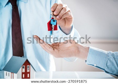 Conceptual Male Realty Agent Giving House Key to a Buyer on Top of the Table with Miniature Model House, Captured in Close up. - stock photo