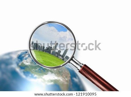 Conceptual mini planet with skyscrapers on it under a magnifying glass. Elements of this image are furnished by NASA - stock photo