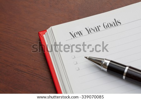 Conceptual,notebook on a wooden table. open diary and pen with new year goals words - stock photo