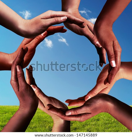 Conceptual peace and unity symbol of different black african ethnicity hands making a circle together on blue sky and green grass background - stock photo