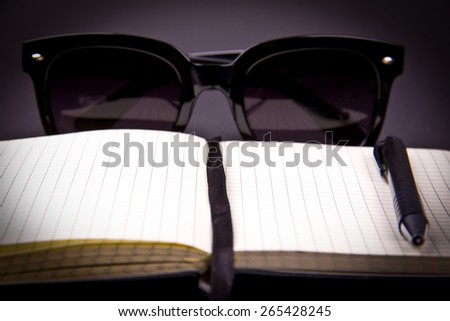 Conceptual photo - bright paper notepad with black bookmark and pen is focused in a middle. Black sunglasses is on back part of composition, blurry. Place for your ideas, thoughts, dreams. Vignetted.