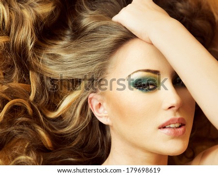 Conceptual photo of attractive young woman posing with amazing makeup and hairstyle.