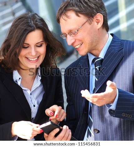 Conceptual photo of businessman showing something in the smartphone to his female assistant