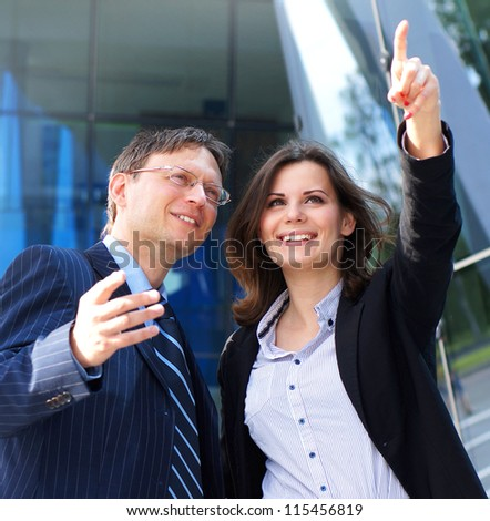 Conceptual photo of businessman showing something to his female assistant - stock photo