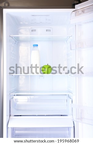 Conceptual photo of diet: apple and milk bottle with measuring type on shelf of refrigerator - stock photo