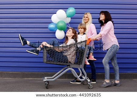 Conceptual photo of happy loving family. Mother and her two daughters children girls and granddaughter with shopping cart and balloons. Outdoors - stock photo