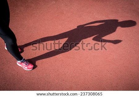 Conceptual photo of shadow of running woman on running track - stock photo