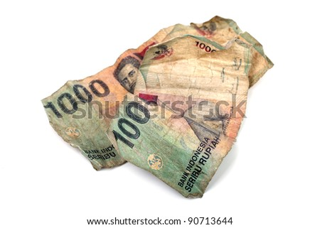 Conceptual photo of two dirty Indonesian banknotes isolated on white background. - stock photo