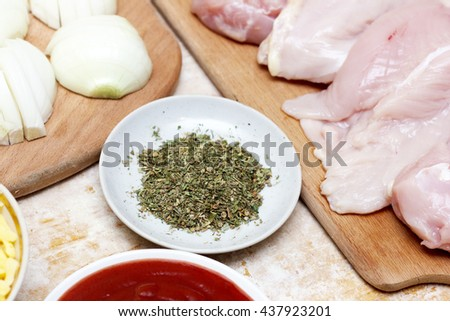 Conceptual photography cooking process home kitchen. Various ingredients on wooden board. The photo shows chicken, spices, red tomato sauce on a white plate - stock photo