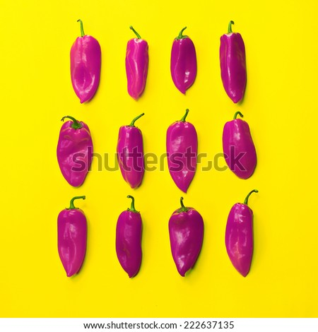 Conceptual photography. set of neatly arranged bright peppers on yellow background for use in design - stock photo