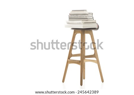 Conceptual Pile of Books on Top of Wooden Leg Chair Isolated on White Background. Emphasizing White Background. - stock photo