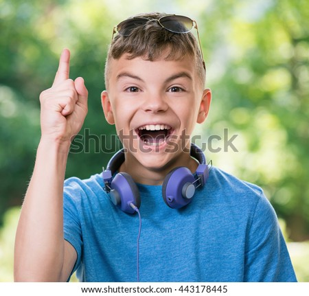 Conceptual portrait of cute teen boy with surprising expression pointing up with finger. Student teenager with headphones and sunglasses posing outdoors. - stock photo