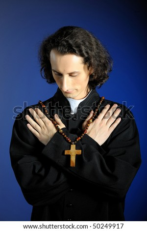 conceptual portrait of Praying priest with wooden cross. blue background - stock photo