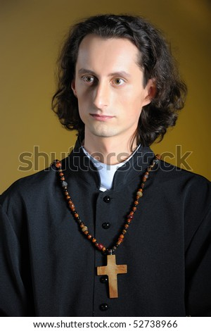 conceptual portrait of Praying priest with wooden cross praying. yellow background - stock photo