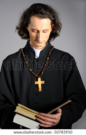 conceptual portrait of Praying priest with wooden cross reading Holy Bible. yellow background - stock photo