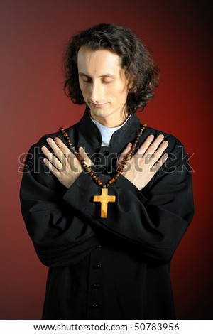 conceptual portrait of Praying priest with wooden cross. red background - stock photo
