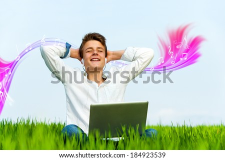 Conceptual portrait of teen boy in green grass field listening to music on laptop. - stock photo