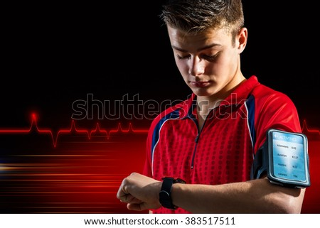 Conceptual portrait of teen sports man reviewing personal records on smart watch. Boy wearing armband with smart phone against abstract dark background.