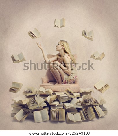 Conceptual portrait of young blonde woman sitting on a chair, reaching out to one of many open floating books, several open books stacked on the floor.  - stock photo