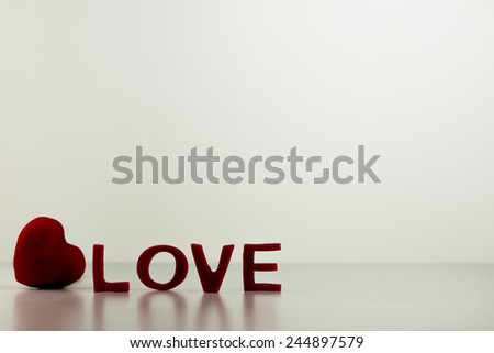 Conceptual Red LOVE Letters with Heart on Top of White Table with White Background. Emphasizing Copy Space. - stock photo