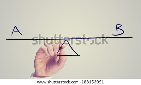 Conceptual retro image of whether to choose plan A or plan B with a man drawing a diagram of a seesaw on a virtual screen balancing the two letters A and B. - stock photo