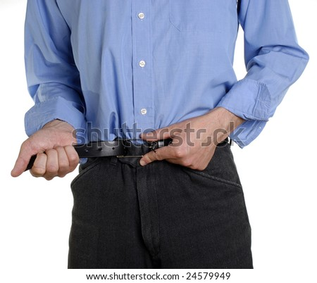 Conceptual shot of business man tightening his belt during tough economic times - stock photo