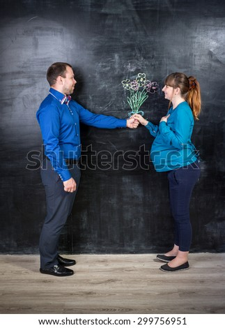 Conceptual shot of handsome husband giving bouquet to pregnant wife against chalk drawing - stock photo
