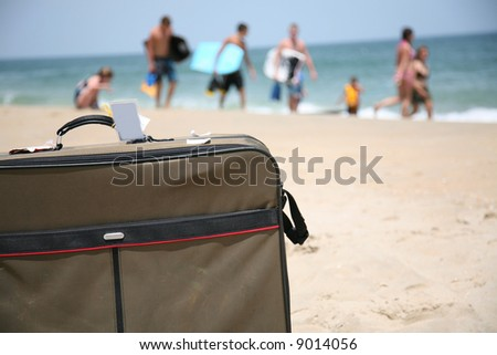 conceptual shot of vacation travel with a suitcase on the beach - stock photo