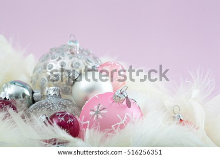 Conceptual still life close up of decorative christmas bauballs together in white feathers against a purple background, textured object, indoors. Xmas occasion shiny decorations, interior space.
