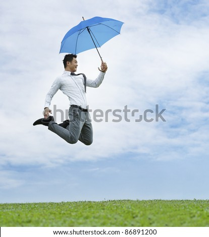 Conceptual Stock image of an Asian business man jumping for joy - stock photo