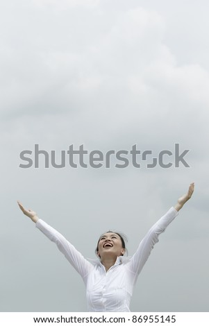 Conceptual stock image of an Asian woman with arms raised - stock photo