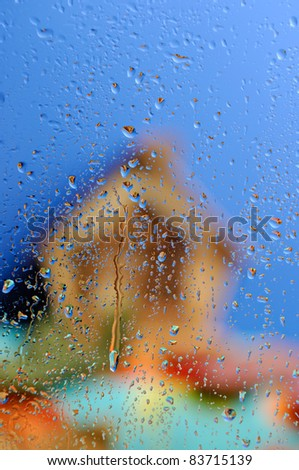 Conceptual stock photo of an Out of focus country house under blue sky behind wet glass in rainy weather - stock photo