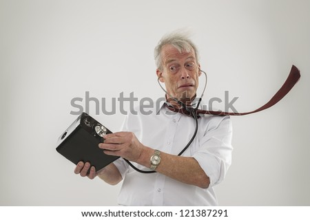 Conceptual studio shot over white of an old man with a hearing problem, who is using a stethoscope to try and hear his audio speakers - stock photo