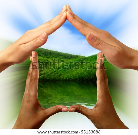 Conceptual symbol home made by black and white people hands framing the nature scenery - stock photo