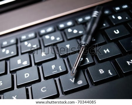 Conceptual view of computer service shown with a screwdriver and keyboard.