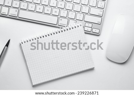 Conceptual White Ballpoint Pen, Clean Spiral Notes, Computer Keyboard and Mouse on Top of White Table with Copy Space at the Center. - stock photo