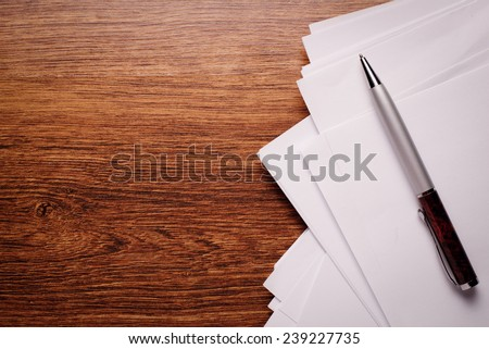 Conceptual White Empty Paper and Ballpoint Pen on Wooden Table Top. Captured with Copy Space on Left Side. - stock photo