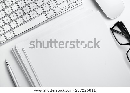 Conceptual White Office Stuffs with Eyeglasses on Top of White Table, Emphasizing Copy Space on Empty White Sheets. - stock photo