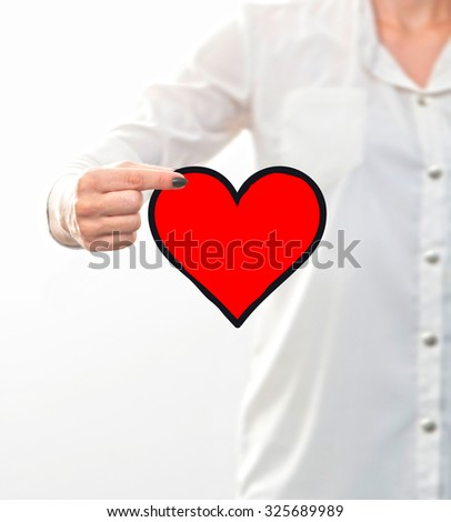 conceptual , woman's hand holding a heart drawing - stock photo