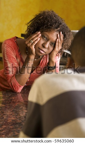 Concerned African-American woman and man in interior setting - stock photo