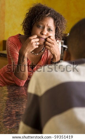 Concerned African-American woman in kitchen - stock photo