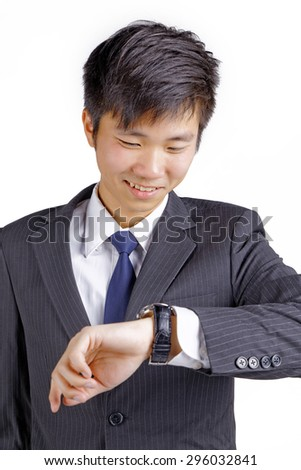 concerned asian business guy looking at his watch - stock photo