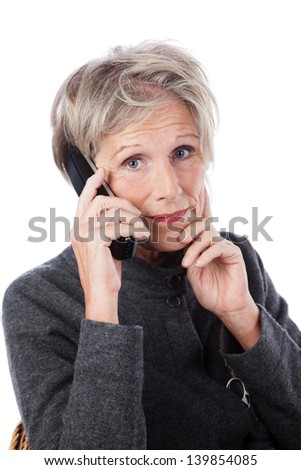 Concerned attractive grey haired senior woman with a worried expression using a wireless telephone isolated on white - stock photo