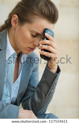 Concerned business woman with mobile phone - stock photo