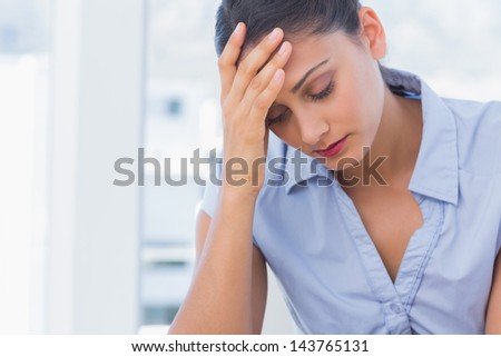 Concerned businesswoman getting annoyed with her work - stock photo