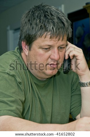 Concerned caucasian male receives bad news on his cell phone - stock photo
