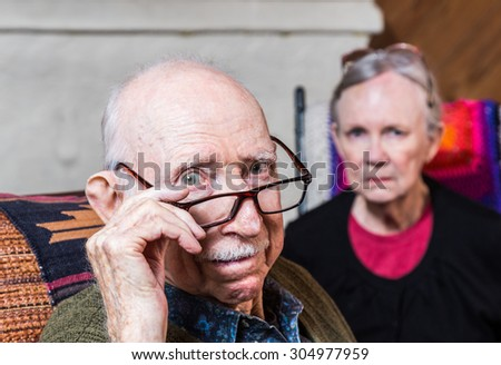 Concerned elderly couple sitting in livingroom scowling - stock photo