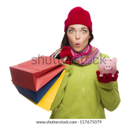 Concerned Expressive Mixed Race Woman Wearing Winter Clothes Holding Shopping Bags and Piggy Bank Isolated on White Background. - stock photo