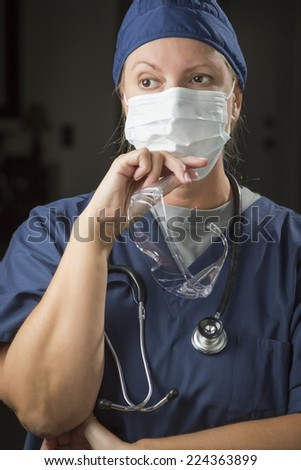 Concerned Female Doctor or Nurse Wearing Protective Face Mask and Holding Protective Eye Glasses. - stock photo