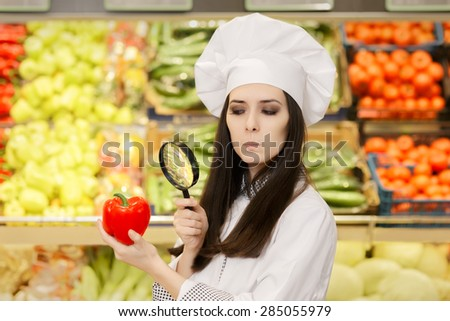 Concerned  Lady Chef Inspecting Vegetables with Magnifying Glass - Portrait of a young female cook in a grocery store checking for best quality ingredients   - stock photo